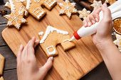 Christmas Bakery. Woman Hands Decorating Homemade Gingerbread House With Icing, Closeup poster