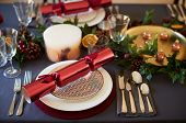 Close up of Christmas table setting with crackers arranged on plates and red and green table decorat poster