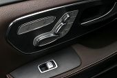 Door Handle With Power Window And Seat Control Buttons Of A Luxury Passenger Car. Brown Perforated L poster
