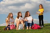 Three girls sit on grass with sheets and look at little girl standing near them and reading text at