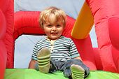 foto of inflatable slide  - 2 year old boy smiling on an inflatable bouncy castle - JPG