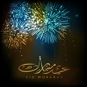 Arabic Islamic calligraphy of golden text Eid Mubarak with firecrackers.