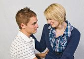 stock photo of forgiven  - The girl is sitting on the boys lap and is asking to be forgiven - JPG
