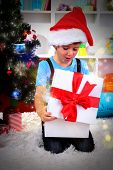 Little boy open his gifts near Christmas tree