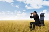 stock photo of binoculars  - Businessman see vision using binoculars on wheat field - JPG