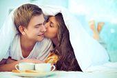 Постер, плакат: Пара наслаждаясь друг друга во время завтрака в постели