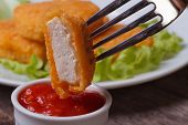 image of impaler  - chicken nuggets impaled on a fork and ketchup closeup - JPG
