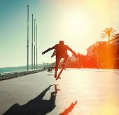 picture of skateboard  - Silhouette of Skateboarder jumping in city on background of promenade and sea - JPG
