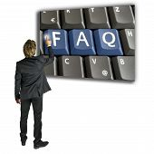 picture of query  - Businessman standing activating a FAQ key on a computer keyboard as he seeks further information and a solution to his problem or query online over the internet - JPG