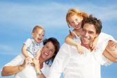 stock photo of family fun  - young happy family having fun outdoors dressed in white and with blue sky in background - JPG