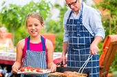 foto of tong  - Father and daughter making barbecue in the garden in summer with sausages and meat - JPG