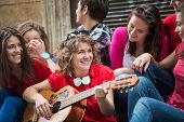 stock photo of adolescent  - Cool adolescents playing music on the city street - JPG
