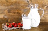 pic of jug  - Ripe sweet strawberries in wooden bowl and jug with milk on color wooden background - JPG