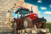 foto of overcoming obstacles  - Brand new Tractor powerfull agricultural working machine breaking through wall - JPG