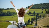 stock photo of scooter  - Young beautiful italian woman sitting on a italian scooter in tuscany outdoor - JPG