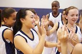 stock photo of 13 year old  - High School Sports Team Celebrating In Gym - JPG