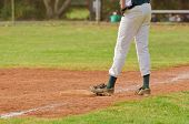 image of infield  - Baseball player wearing green socks and jersey standing on a third base - JPG