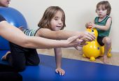 pic of chiropractic  - a female physiotherapist makes physiotherapy with young children - JPG