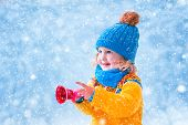 foto of christmas bells  - Adorable little girl cute toddler in a blue knitted hat and yellow nordic sweater playing with Christmas toy bell catching snow flakes having fun outdoors in a beautiful winter park - JPG