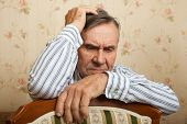 image of single man  - Elderly man grieves at home - JPG
