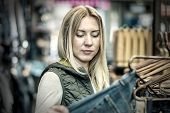 picture of boutique  - Beautiful blonde female looking jeans in the boutique - JPG