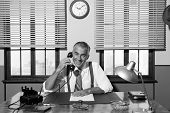 stock photo of 1950s  - Smiling handsome businessman on the phone working at desk 1950s vintage office - JPG