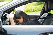 picture of deprivation  - Closeup portrait tired young attractive woman with short attention span driving her car after long hours trip trying to stay awake at wheel isolated outside background - JPG