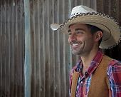 stock photo of wrangler  - A cowboy leans against a metal wall and smiles - JPG