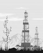 image of oilfield  - Oil rigs at oilfield over mountain range - JPG