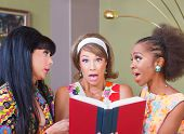 stock photo of tawdry  - Three diverse pretty women surprised with a book - JPG
