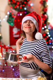 picture of finger-licking  - Woman tasting something licking her finger on Christmas - JPG