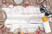 stock photo of suntanning  - Suntan lotion and sea shells make frame on wooden surface - JPG