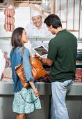 image of slaughterhouse  - Mature couple using digital tablet while standing at counter of butcher shop - JPG
