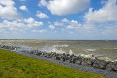 stock photo of dike  - Storm raging over a lake along a dike in spring - JPG