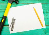 pic of tool  - Working tools. A paper with pencil and the working tools on wooden, green background.
