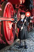stock photo of nostalgic  - Little child boy as nostalgic railroad conductor with cap and signaling disk beside large wheels of a steam locomotive - JPG