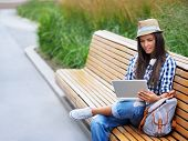 pic of work bench  - Young girl on a bench with a laptop - JPG