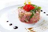 foto of tartar  - Tuna tartar serving on white clean plate with caviar and rocket salad - JPG
