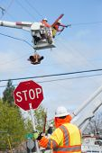 image of lineman  - A traffic guard holds a stop sign as two power line repairmen hover in the sky repairling an electric line - JPG