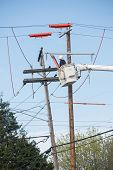 stock photo of lineman  - A lineman high in a truck bucket works to repair electric lines - JPG