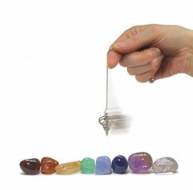 stock photo of pendulum  - Hand holding a moving spiral pendulum over eight chakra colored tumbled gemstones on a white background - JPG