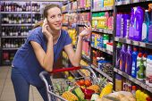 foto of supermarket  - Pretty woman having a phone call and pushing trolley at supermarket - JPG