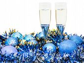 stock photo of sparkling wine  - two glasses of sparkling wine at blue Christmas balls and tinsel isolated on white background - JPG