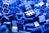 Pile of blue color building blocks with selective focus and highlight on one particular block poster