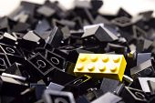 Pile of black color building blocks with selective focus and highlight on one yellow block poster