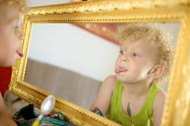 picture of sticking out tongue  - a little child sticking his tongue in the mirror - JPG