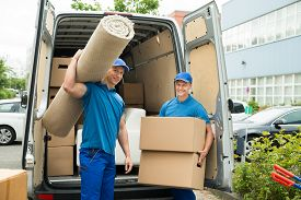 image of moving van  - Two Male Workers Carrying Carpet And Cardboard Boxes In Front Of Van - JPG