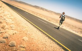 picture of street-walker  - Lonely man walking along the road among the namibian african desert  - JPG