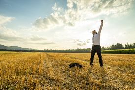 stock photo of stressless  - Young Businessman Standing in the Field and Raising his Arm for Success While Throwing his Coat on the Ground - JPG
