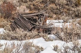 stock photo of outhouse  - Neglected outhouse laying in the snow in a ghost town - JPG